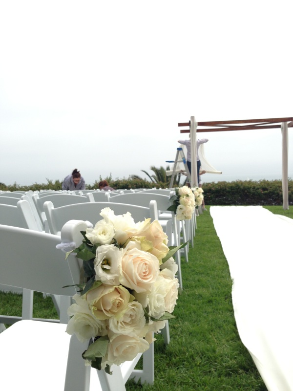 Creating the ceremony site.   The Chuppah was draped in yards of chiffon.  Fabric was laid down to create the aisle runner.
