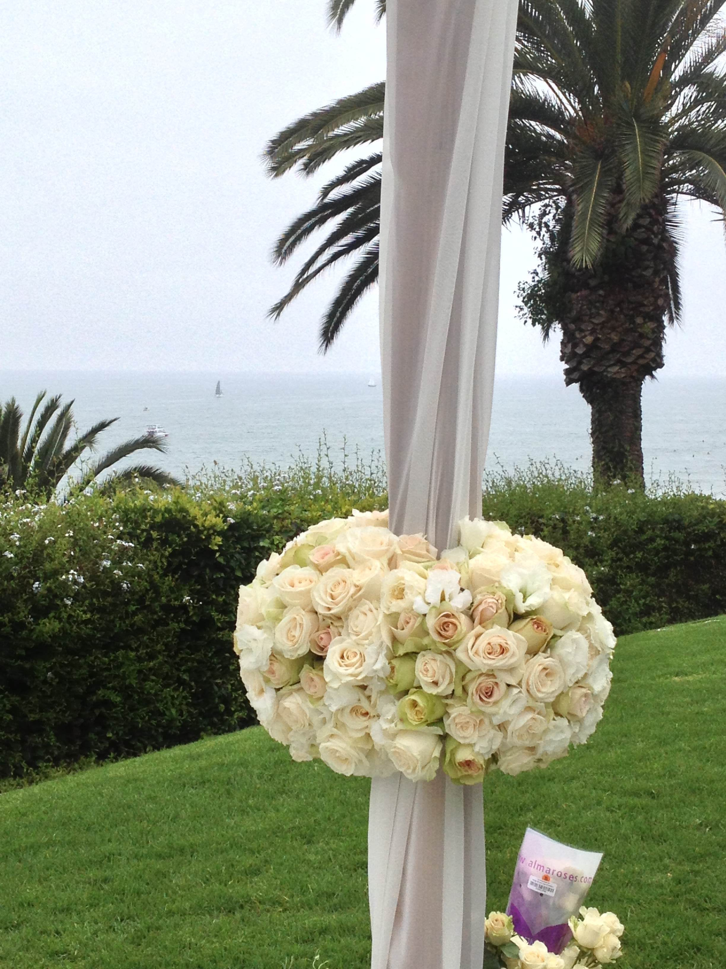 A close up view of the floral tie backs attached to the Chuppah.