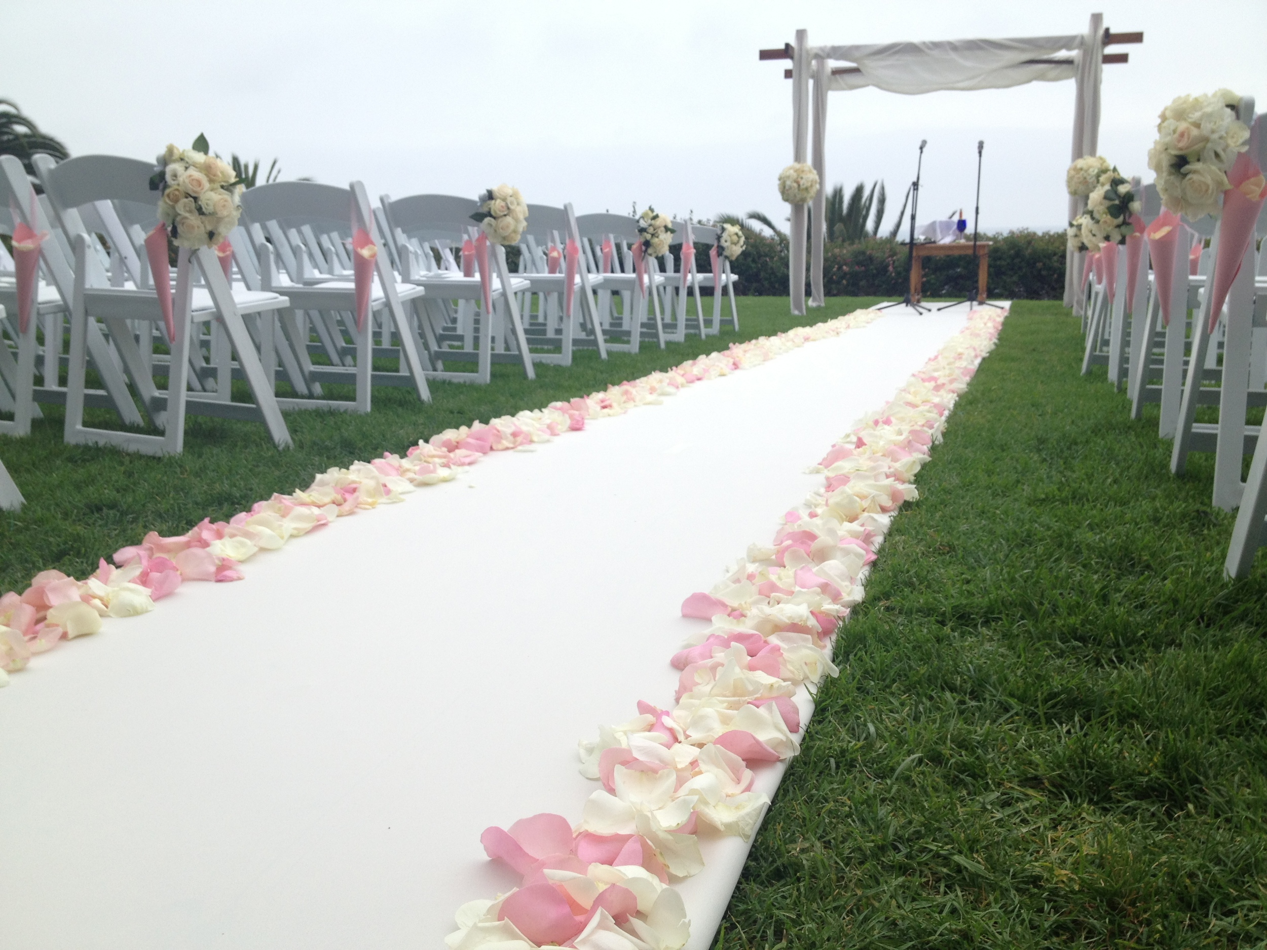 The completed ceremony site with Chuppah, aisle runner and petals, chair decor and paper cones filled with white roses petals. Now on to the reception.