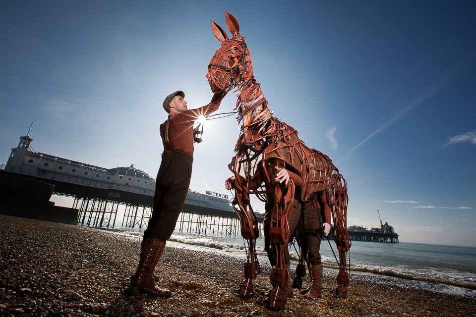 War Horse was on tour, and this is your typical PR photo to announce his visit to Brighton. Bright and sunny, I stopped it right down to darken the sky, and if you can partly obscure the sun, you get the starburst effect. I then used two 600EX flashes from the right on full (or nearly full) power to light Joey (horse) and the person's face, with a third flash lighting Joey's body. There may have been a fourth filling in from the left, but it doesn't look like it's doing much.  A silhouette might have been another option, but it didn't work as it the shape was too busy. We also tried Joey rearing but this didn't work either as we lost his face, the eyeline connection with the person holding him, and it also looked rather messy with bodies etc.  Despite Joey being a model, you still look at his eye first, and that led the approach to the picture.