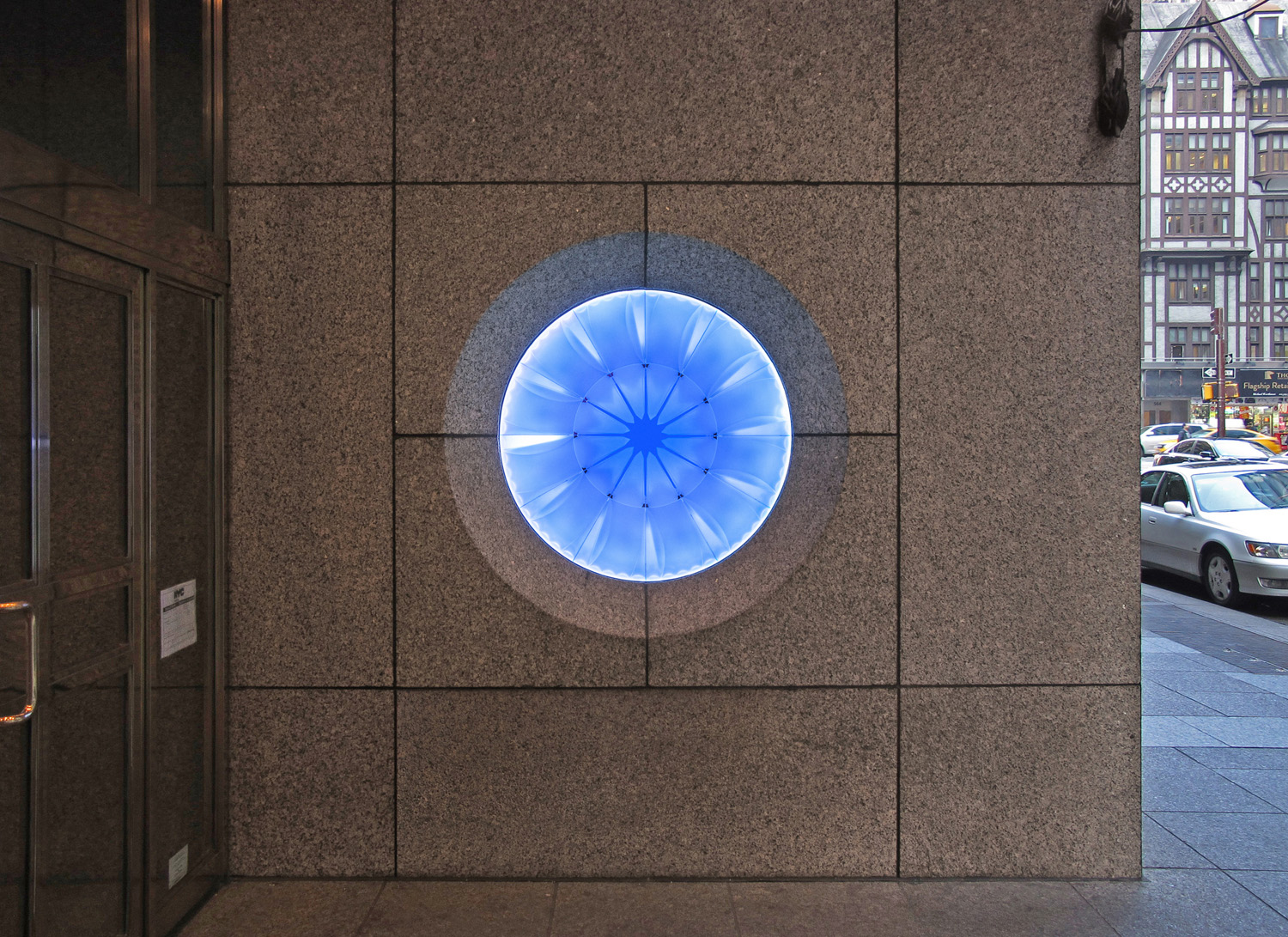 Voyage   2015. Cast glass, plate glass, aluminum, stainless steel, LED lights. 45 inch diameter face.555 Fifth Avenue, New York, NY