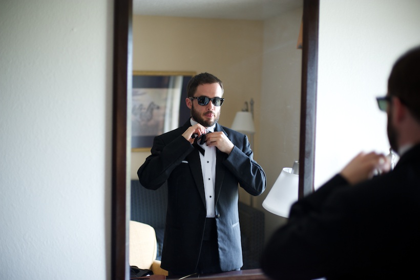 Wedding day getting ready photo by Josh Glessner of Glessner Photography of a groomsman in sunglasses tying a bowtie in the mirror at the backyard wedding of J.P. Perkins and Katherine Henry in Asheboro, NC