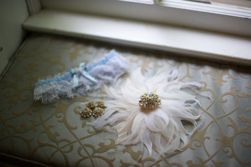 Wedding day detail photo by Elizabeth Glessner of Glessner Photography of Kate Spade earrings and broach from Rent the Runway and feather sash by Alice Hart Couture Millinery via Etsy at the backyard wedding of J.P. Perkins and Katherine Henry in Asheboro, NC