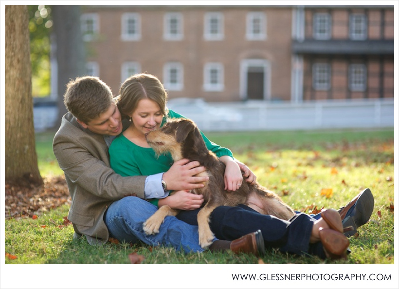 Young couple with dog in engagement photo in Old Salem in Winston-Salem, NC