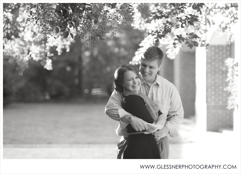 Black and white image of couple embracing and laughing at Old Salem