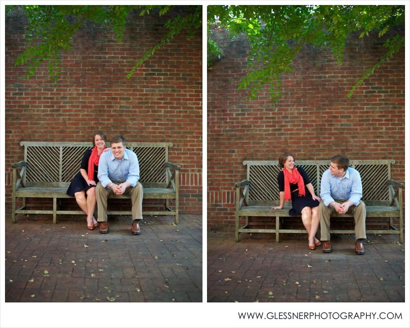 Engagement photo of couple sitting on bench underneath the Heritage Bridge at Old Salem