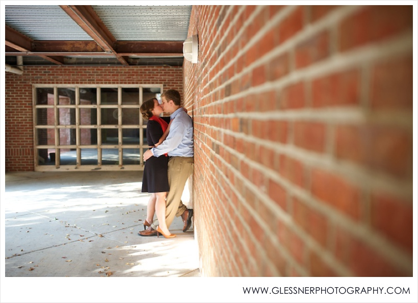 Engagement photo of couple kissing against brick wall in Old Salem