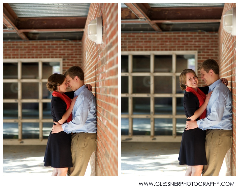 Engagement photo of couple embracing against brick wall in Old Salem