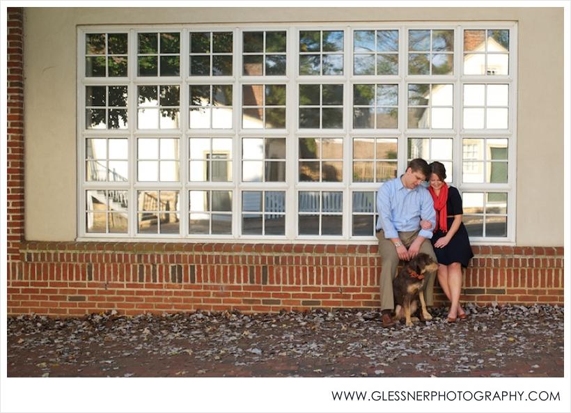Couple sitting on brick ledge with dog outside of Old Salem Museum