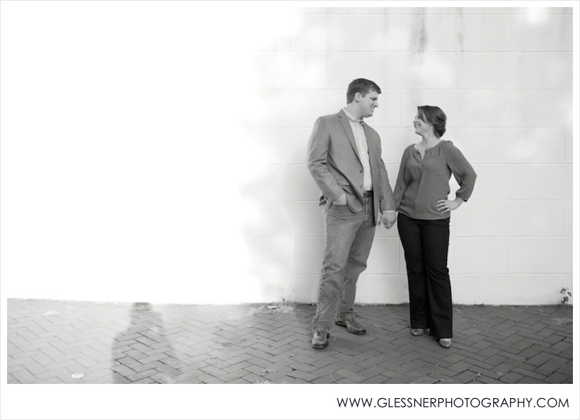 Black and white engagement photo of couple holding hands in Old Salem