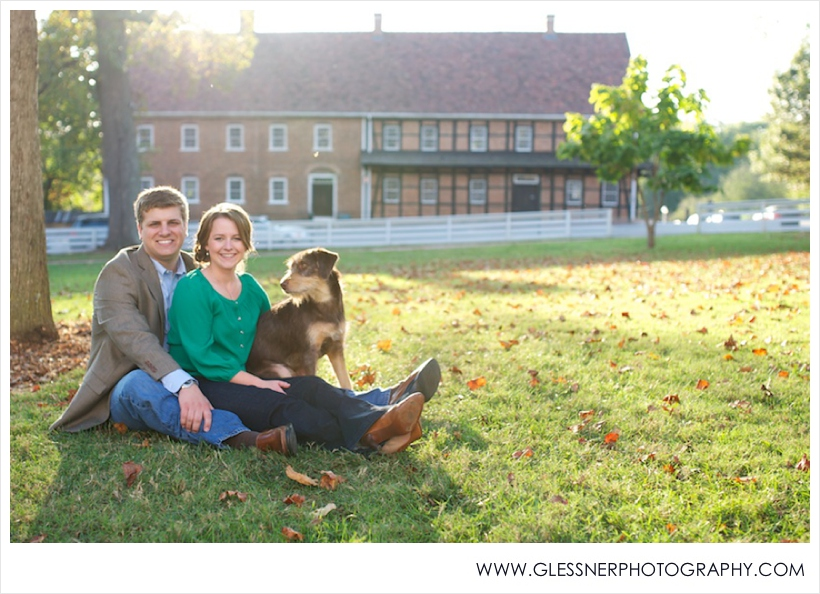 Engagement photo of couple sitting on lawn with dog at sunset in Salem Square in front of Salem College