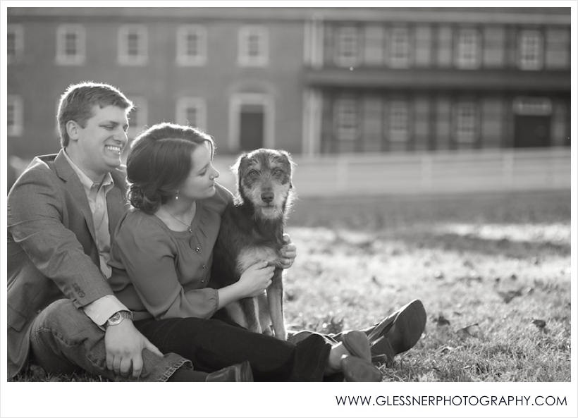 Black and whiteengagement photo of couple sitting on lawn with dog at sunset in Salem Square in front of Salem College