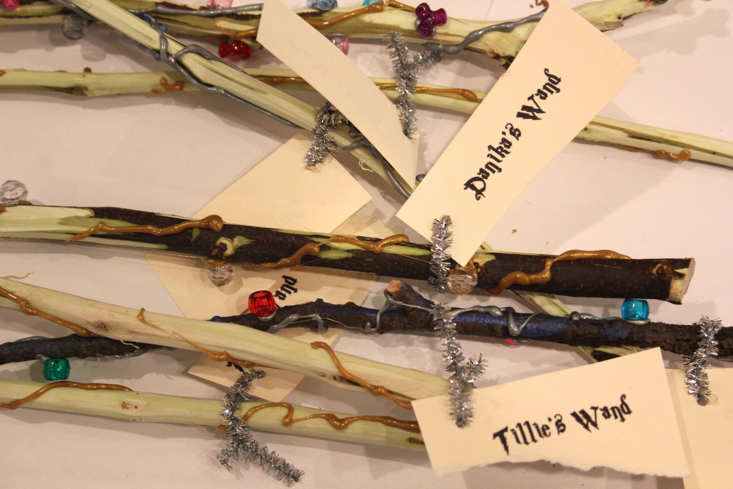 Wands (twigs) decorated with beads and sliver/gold hot glue.