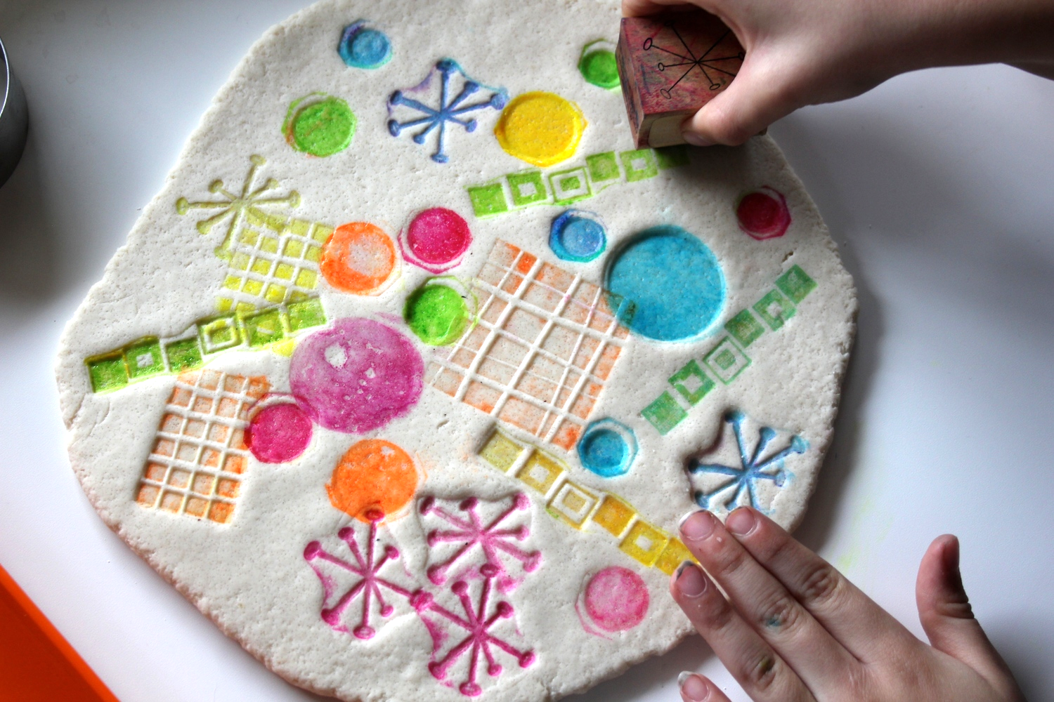 Gently press the inked stamp into the rolled dough. To get the best results be sure to wipe your stamp with a damp paper towel before using a new color. Think of this as a salt dough canvas!