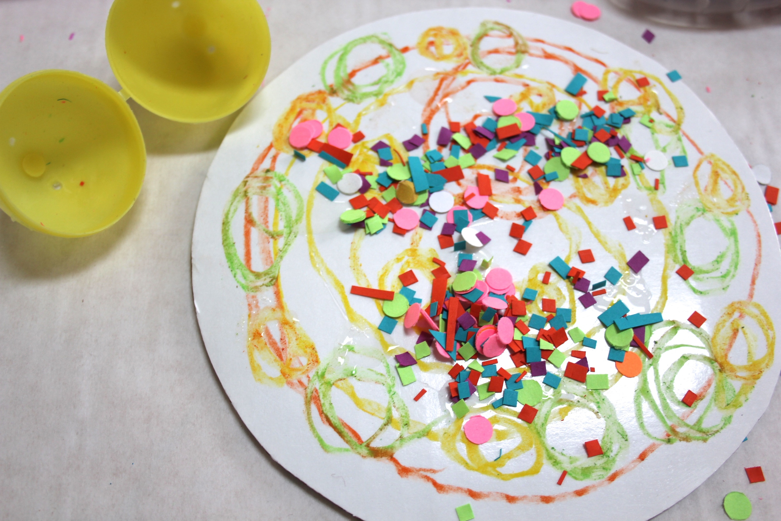 Think about where you want your confetti to land and dribble some glue to those areas. Crack open your confetti filled egg and wait for the colorful 'egg-plosion'. Super fun surprise for little ones.