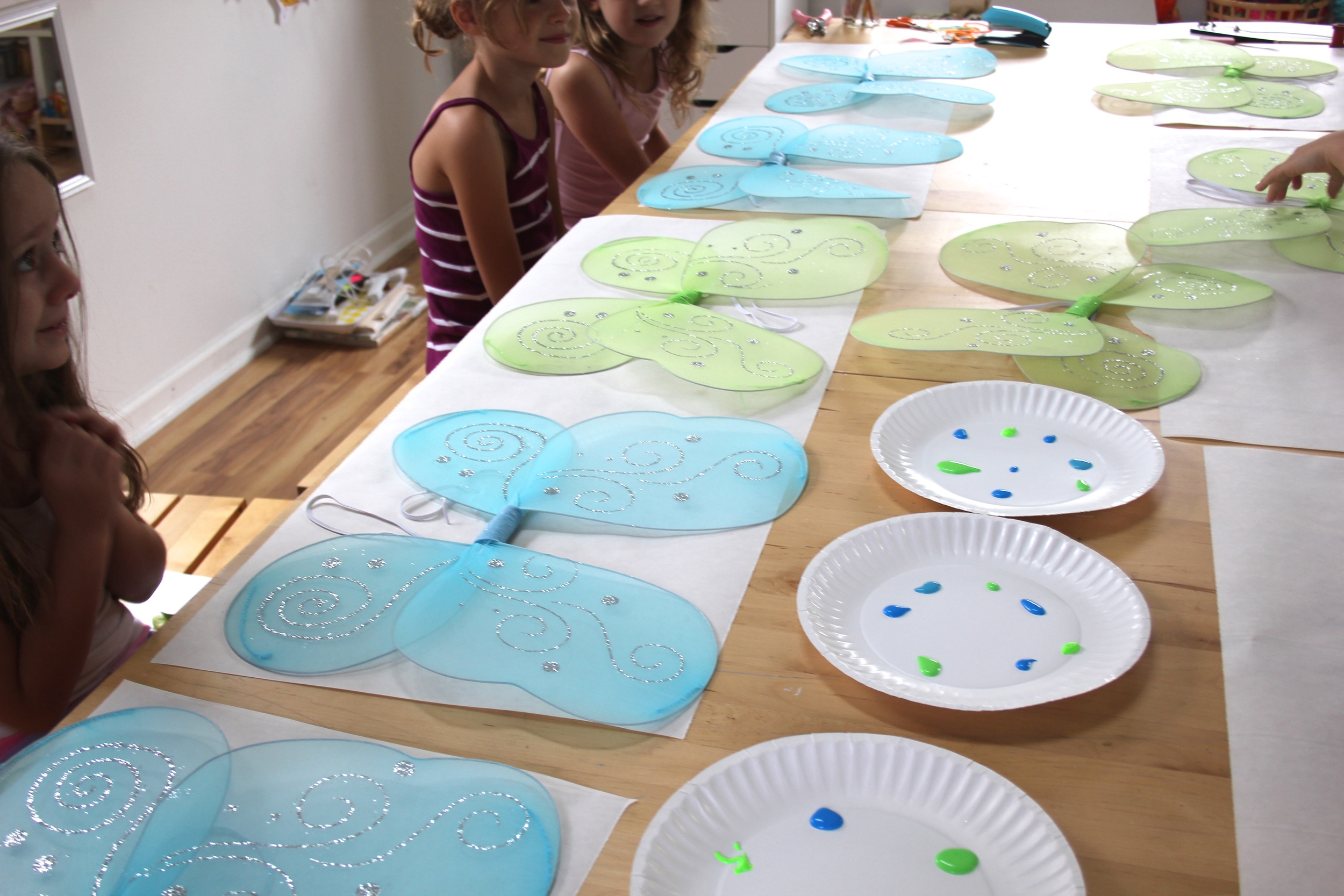 A table of fairy wings ready to be painted and clothesline dried.