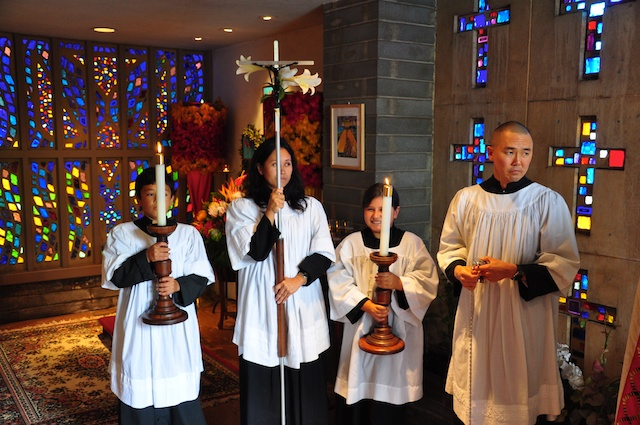 Michel serving as the crucifer on Easter Day with her children