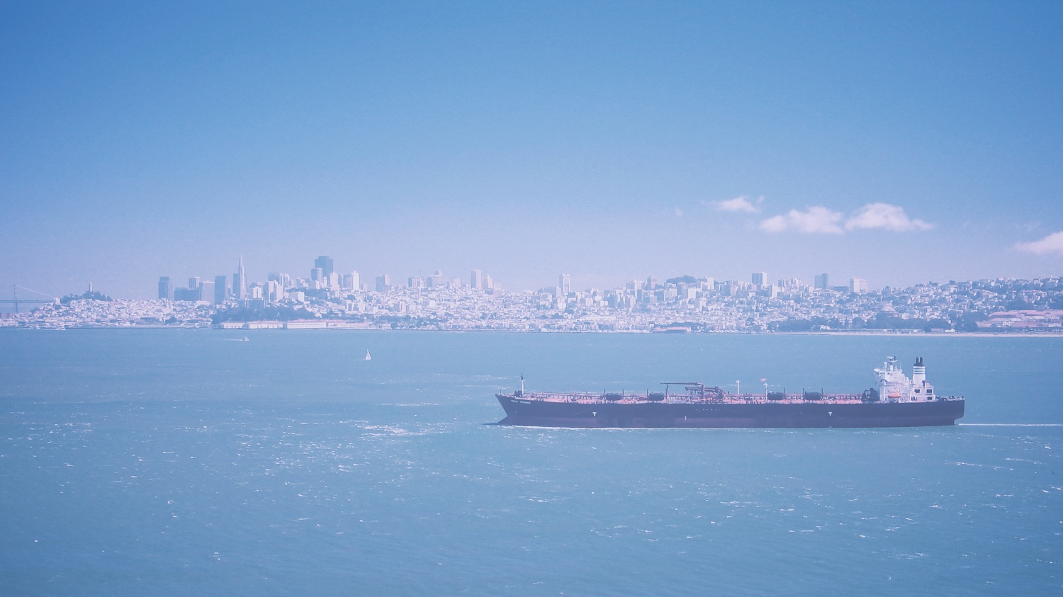 A cargo ship travels in the San Francisco Bay with the city skyline in the background