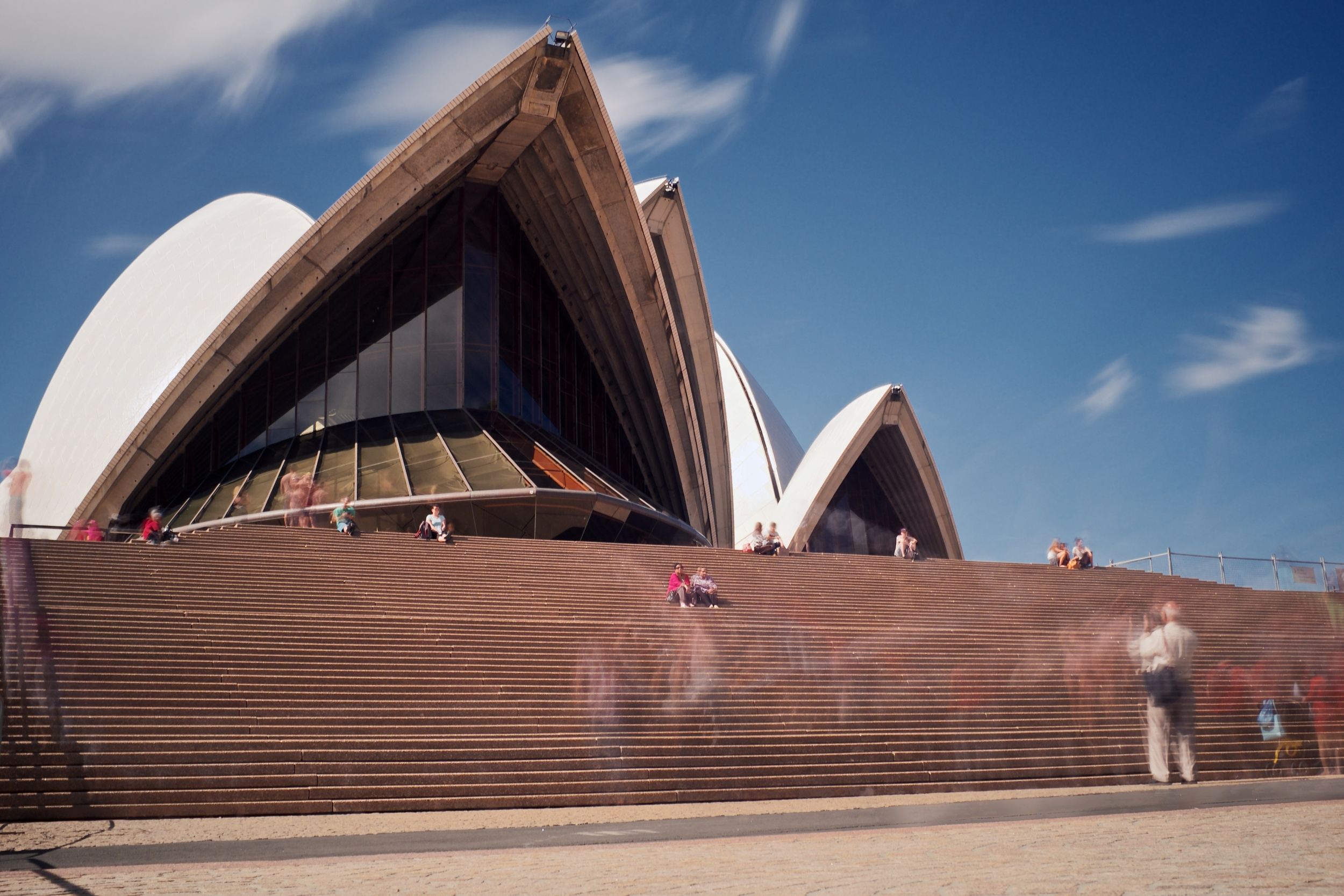 A long exposure photograph of the Sydney Opera House in midday sun.