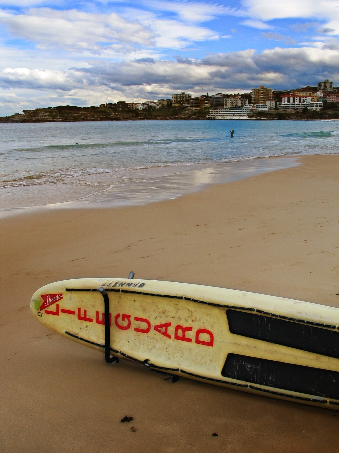 The traditional lifeguard's surfboard and a lonely woman surfer in the background at famous Bondi Beach, Australia. Shot in the winter of 2004.