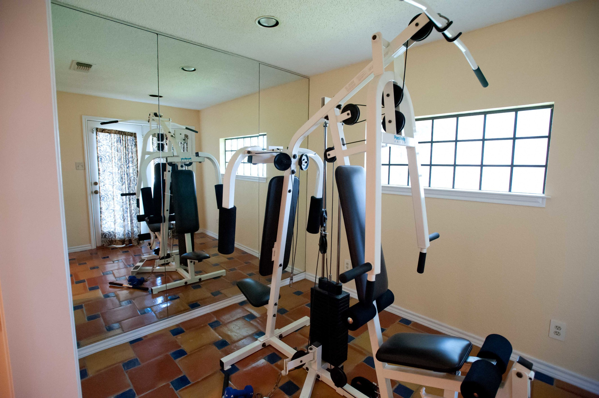 Adjacent to the bathroom was a mirrored workout room, with doors (not seen here) opening up to the backyard.