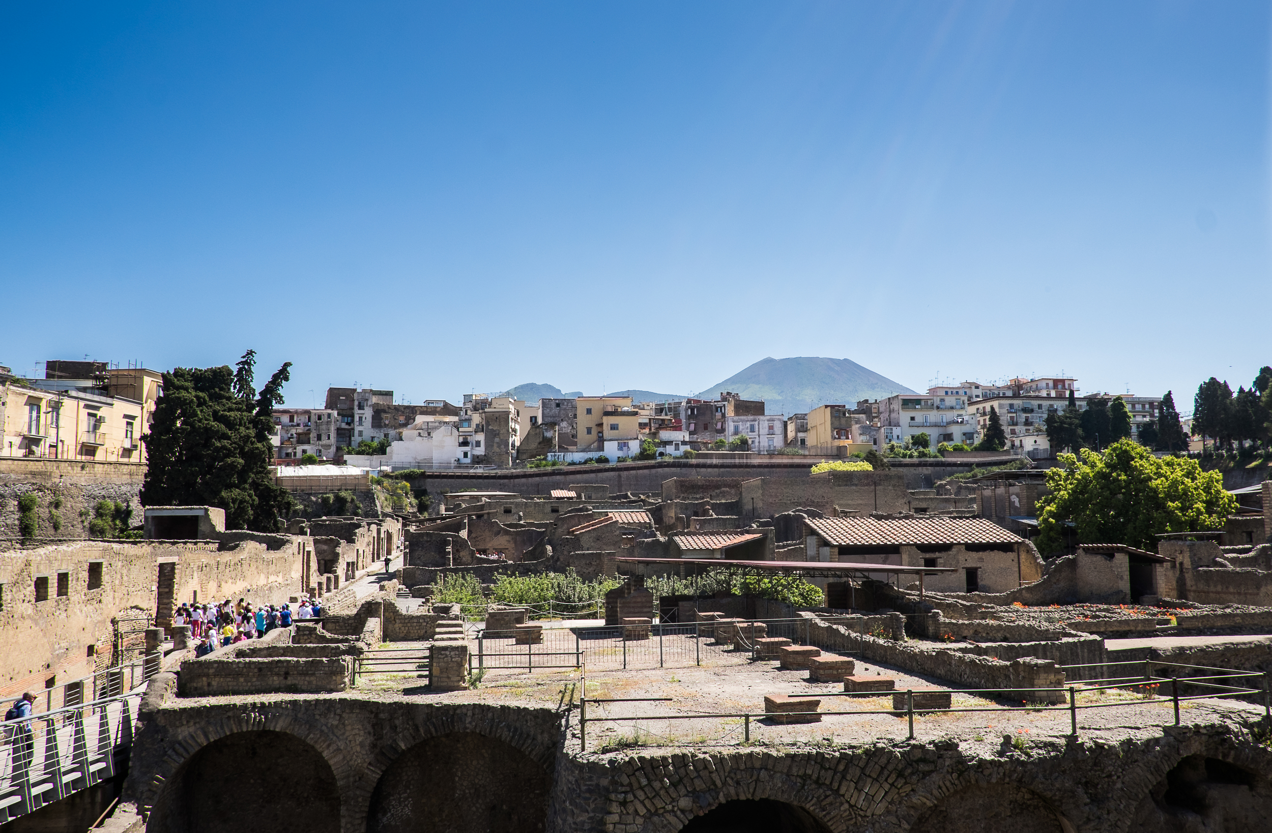 In 79 AD, this city was buried with volcanic mud from Mount Vesuvius -- seen in the background -- similarly to how Pompeii was buried in volcanic ash. The mud did a superior job of preserving this site; roughly 20% of the city has been excavated. The rest cannot, due to the modern-day city of Ecolani which sits on top of it, seen in the middle-ground.