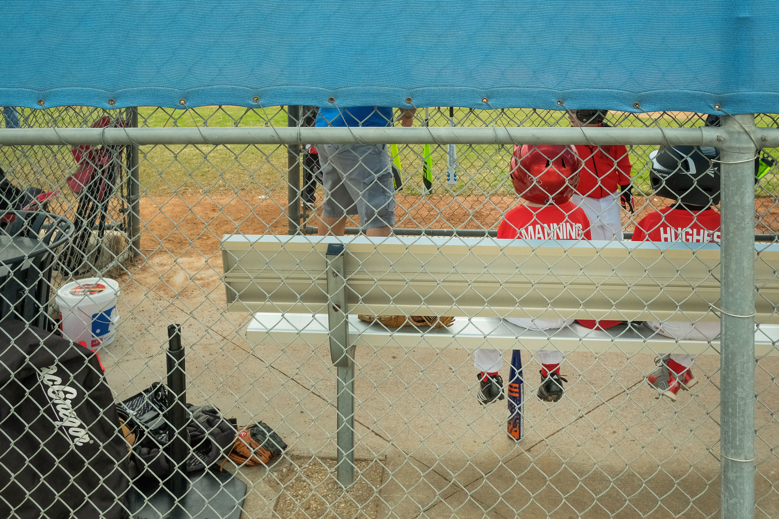 Watching the boys climb onto the dugout bench is really funny.