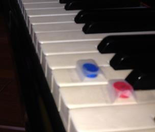 Tiny colored magnets taped to the keys provided just the right amount of tripping.  These  would work, but I used the ones from my magnetic grand staff.