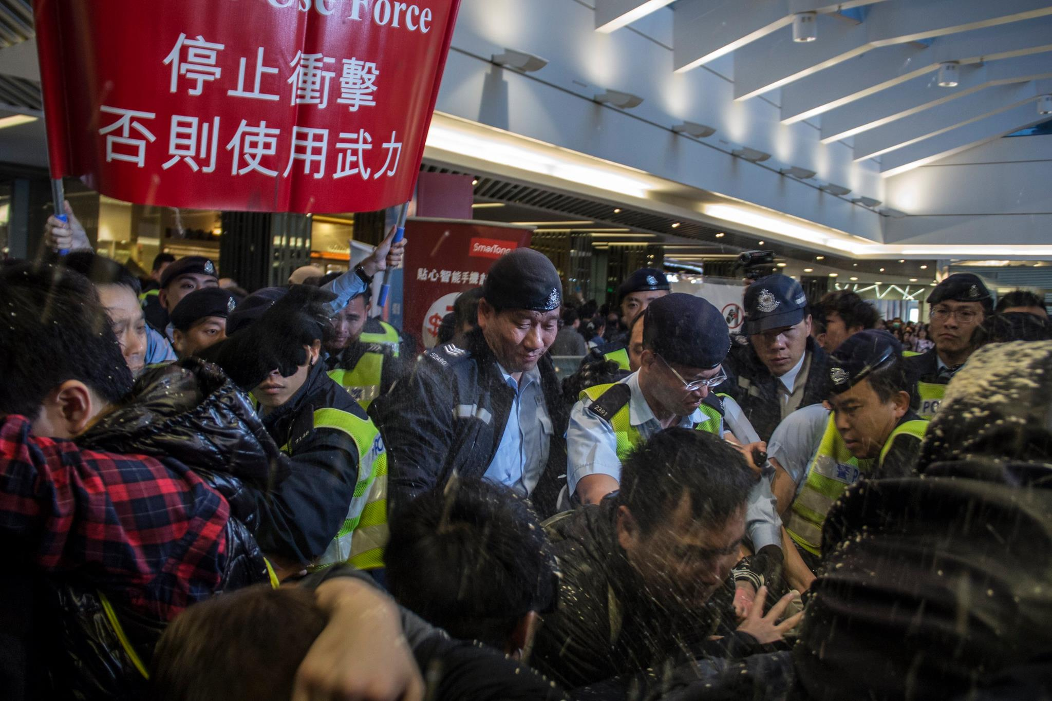 Pepper spraying protesters fighting against parallel traders overwhelming Hong Kong.