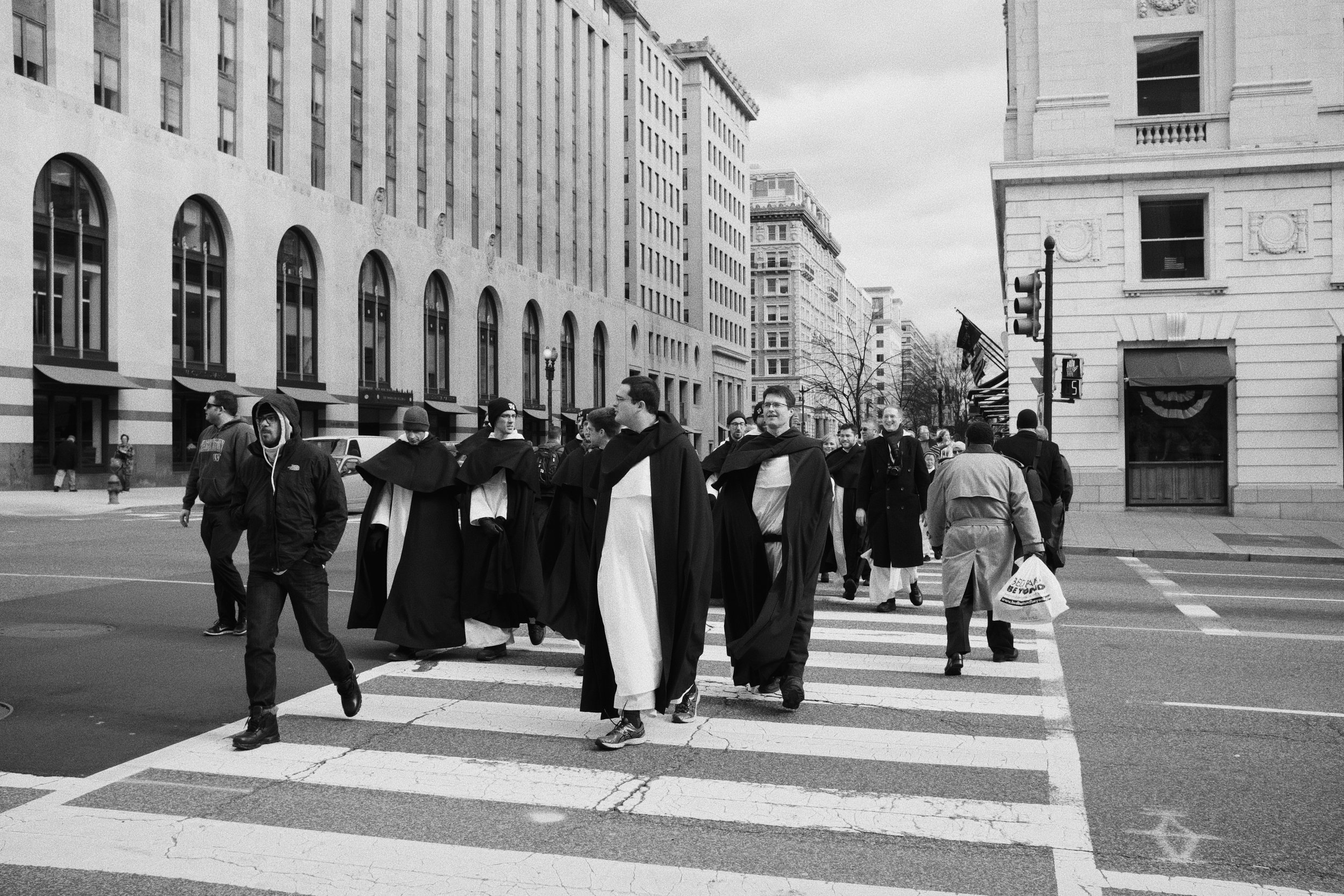 A group of friars crosses the street on the way to the march.