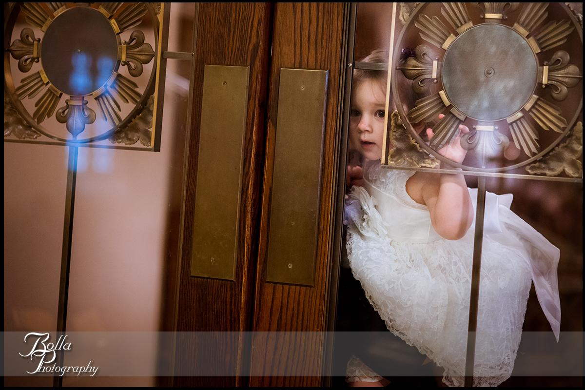 010-Bolla-Photography-wedding-Belleville-IL-ceremony-church-flower-girl-watching-through-door-Wilson.jpg
