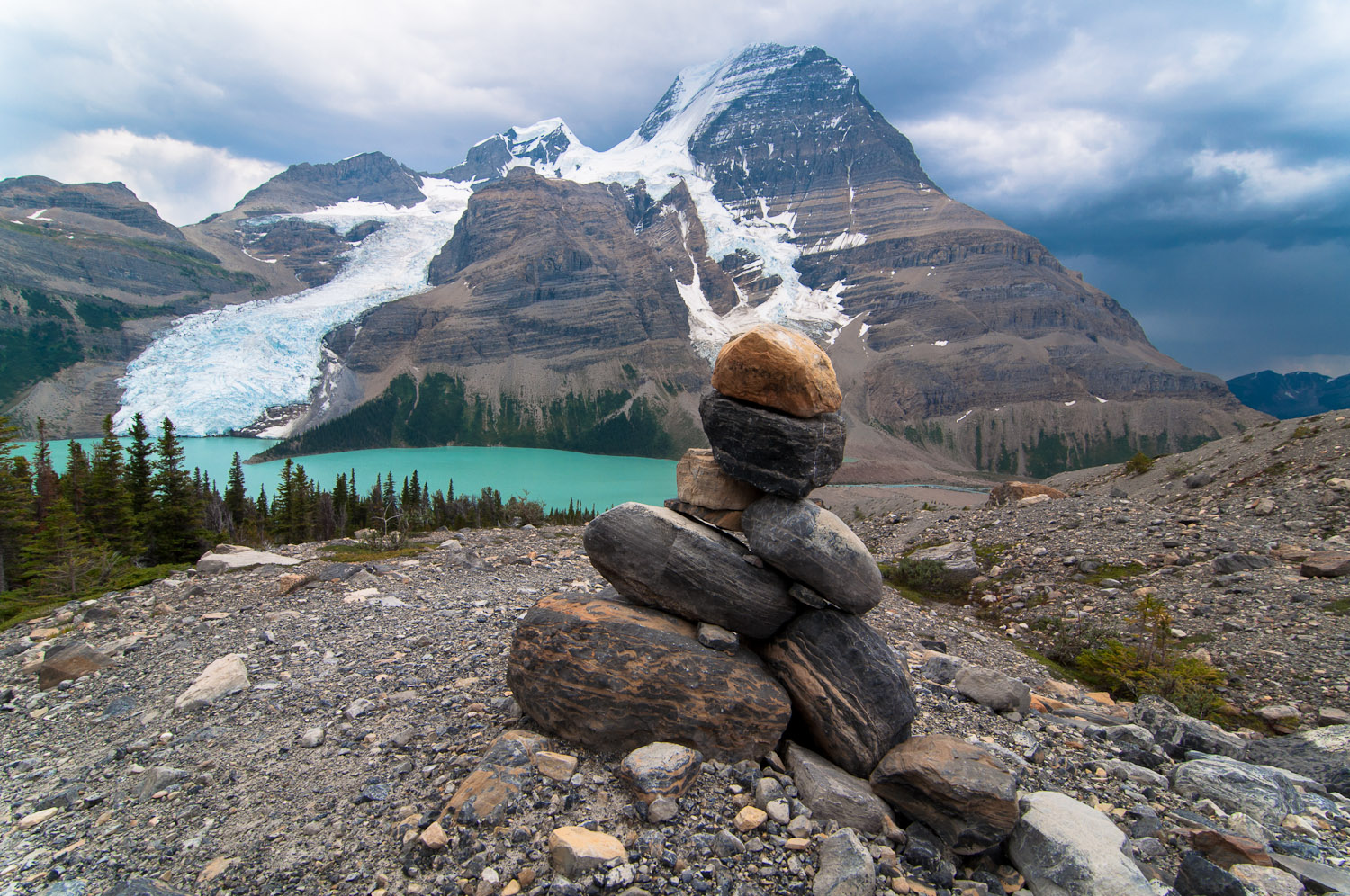 A cairn on the trail as we look down on Berg Lake, Berg & Mist glacier, as a storm rolls in over Mt Robson.
