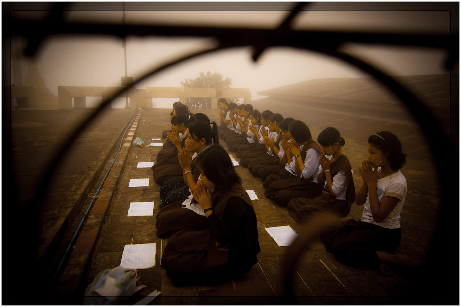 High up in the clouds at dawn, schoolgirls chant at the monestary on top of Mt Zwegabin - Burma / Myanmar