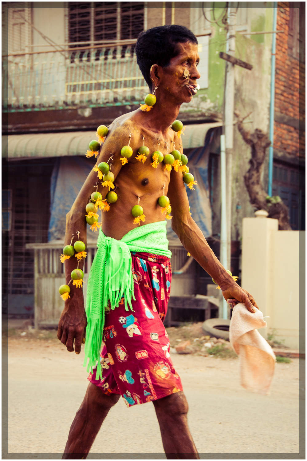 I was told that this man from the neighborhood has few belongings, but has faith that runs deep.  His body had over two dozen limes hanging from metal hooks in his skin.  © Dustin Main 2013