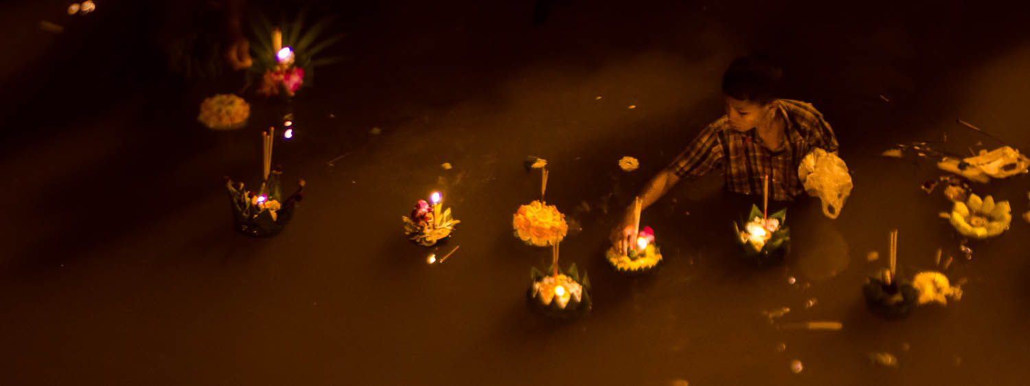 A boy is raiding the river during Loy Krathong in Chiang Mai, Thailand