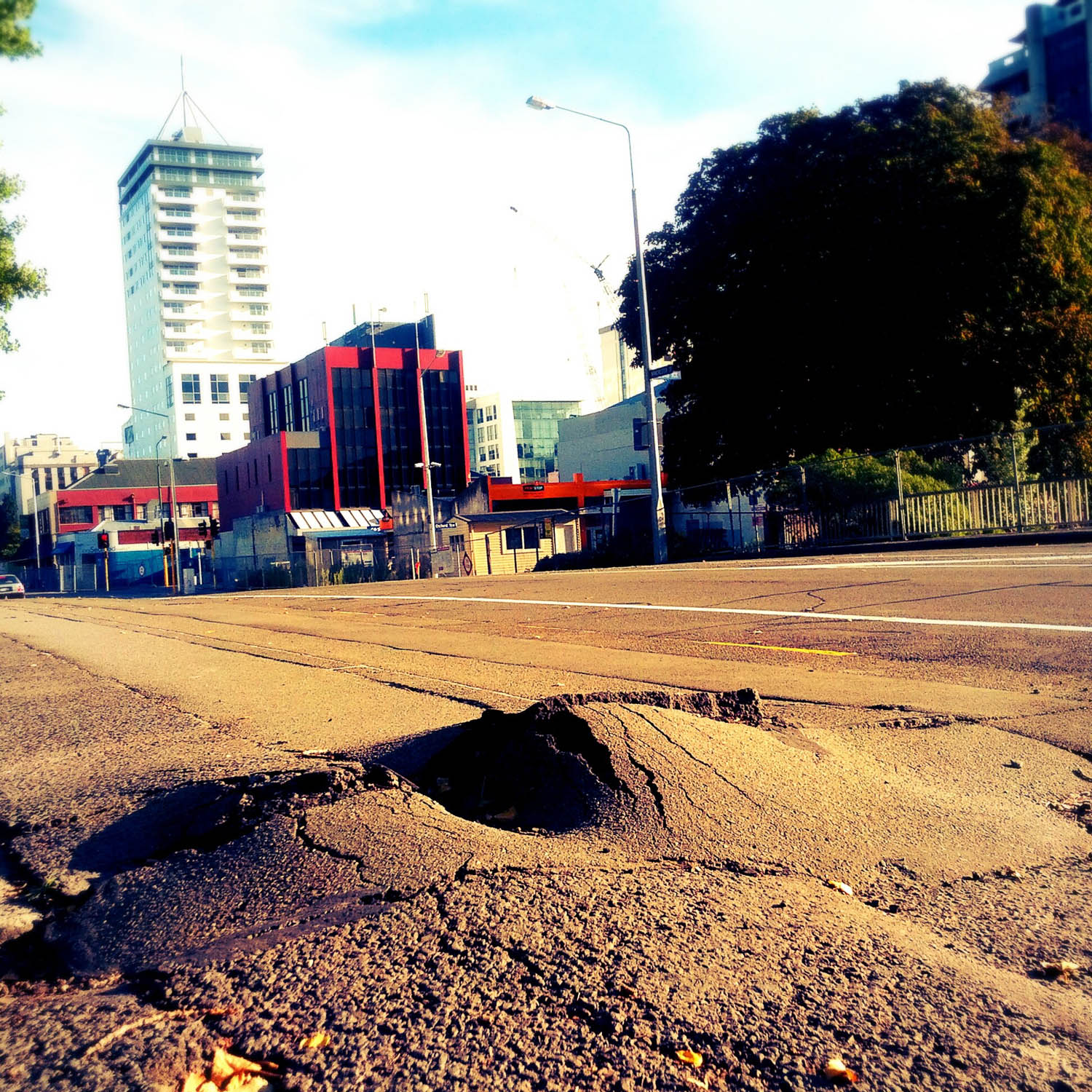 Uplifted sidewalk on a bridge in Christchurch. A relatively small reminder of the destructive nature of earthquakes. Buildings in the background in the process of being demolished.