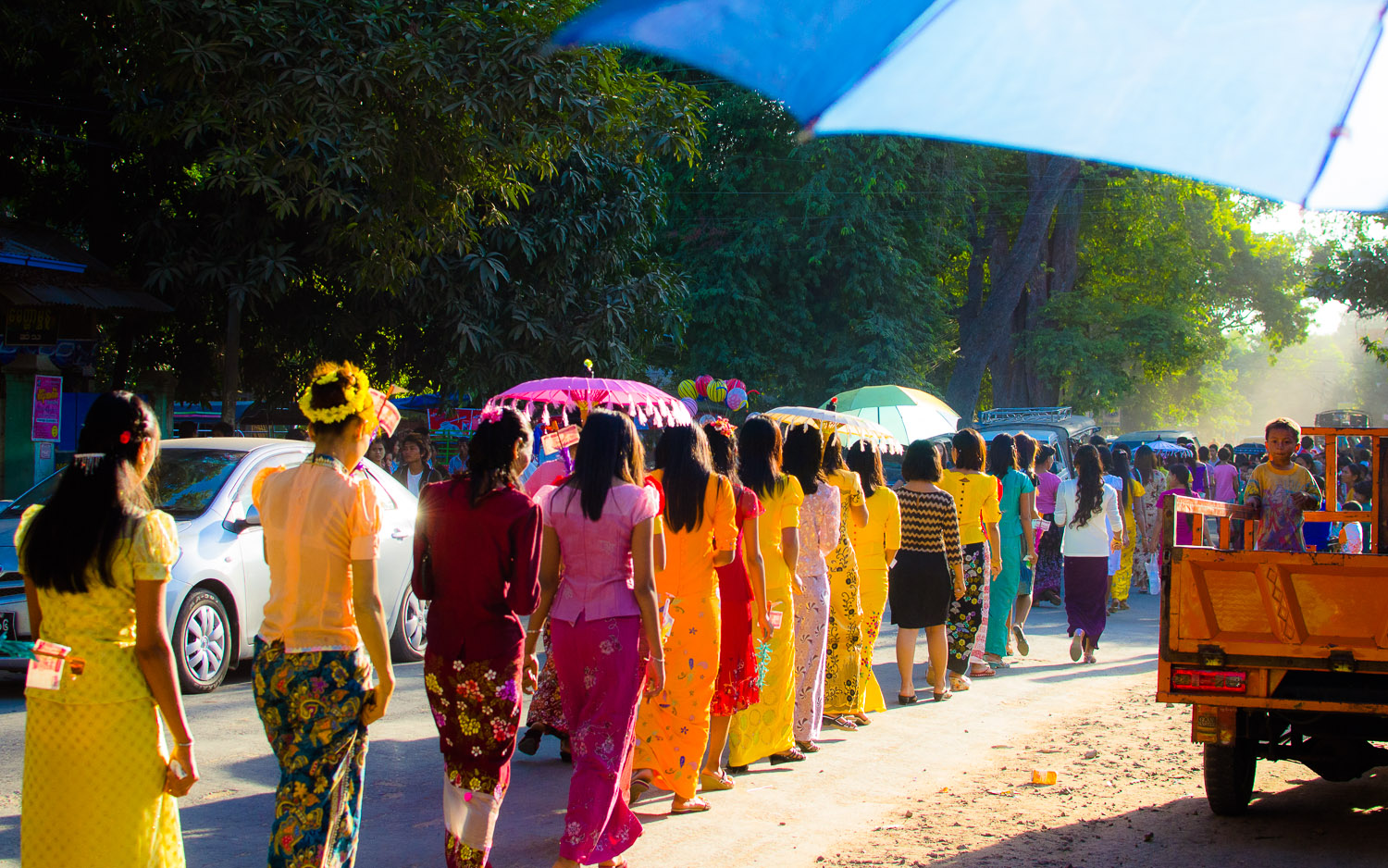 A row of women walk down the street as the procession moves toward Shwezigon Pagoda in Nyaung U, Myanmar (Burma).  © Dustin Main 2014