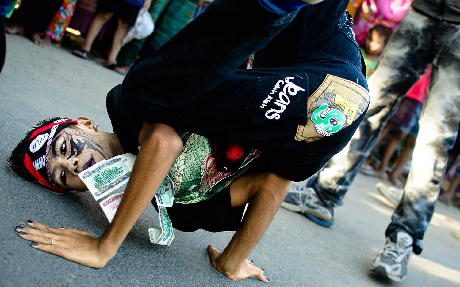Break-dancing on the streets, with money pinned to the shirt to be given as an offering at the pagoda.  © Dustin Main 2014