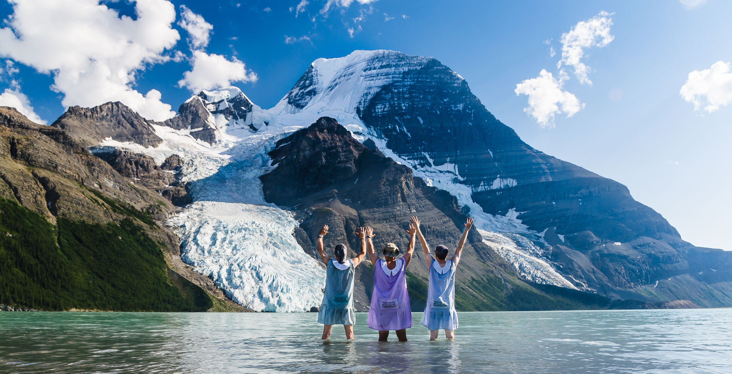 Hikers Without Pants 2012.  Three men in dresses knee deep in a glacial lake looking out towards Mt Robson.   © Dustin Main 2013