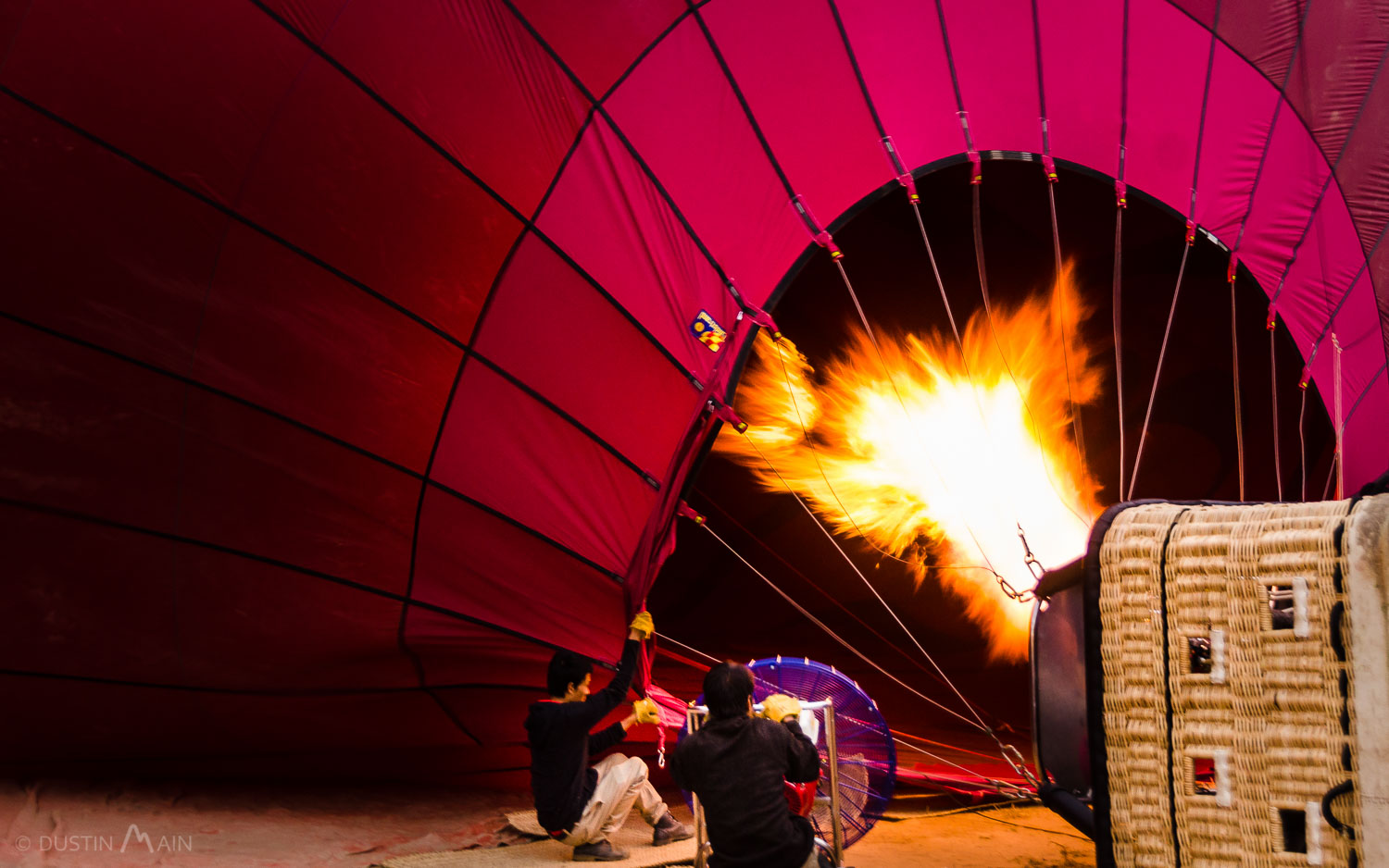 Burners are on full blast as the staff push air into the balloon in Bagan. © Dustin Main 2013