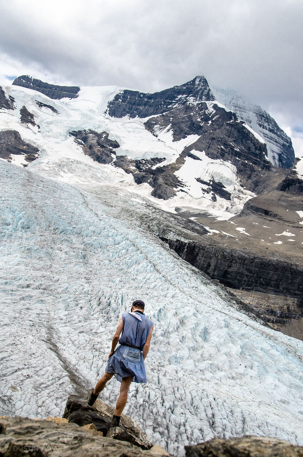 On the edge of a cliff, l ooking out over the massive Robson Glacier, with Mt Robson (the highest mountain in the Canadian Rockies) in the background.   © Dustin Main 2012