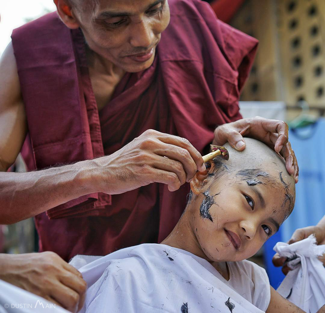 A young novice monk has his head shaved before he enters the monastery for a week in Yangon, Myanmar. © Dustin Main 2016