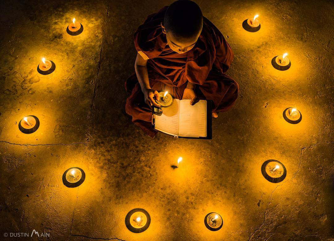 A novice monk by candlelight in Myanmar. © Dustin Main 2016