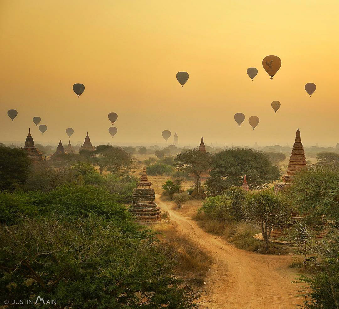 A yellow and hazy sunrise dotted with hot air balloons well into dry season in Bagan, Myanmar. © Dustin Main 2016