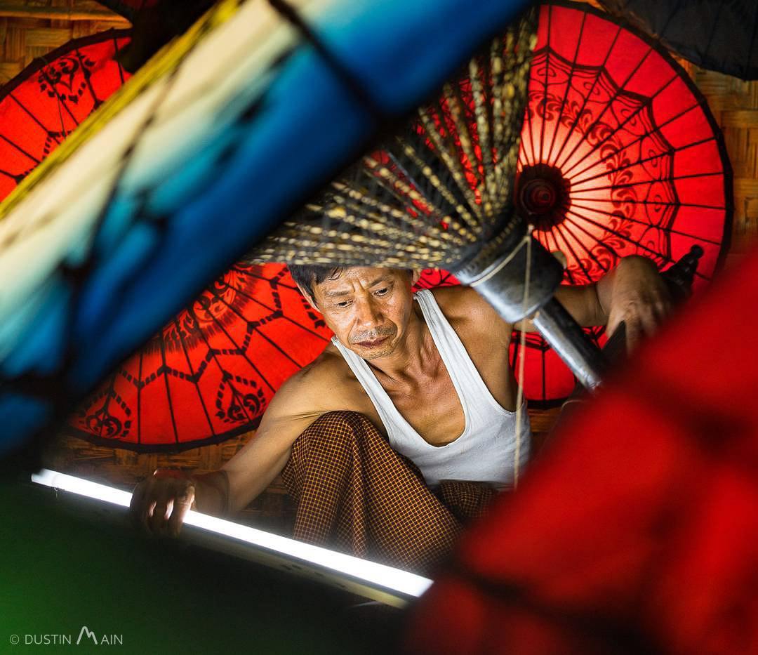 U Aung Soe pieces together parasols at night to cover the cost of the family health care bills. © Dustin Main 2016