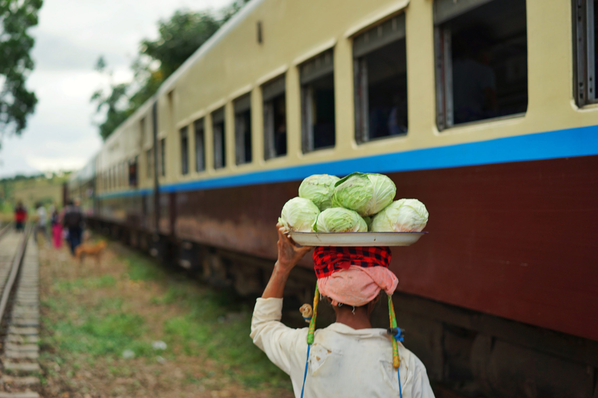 Food seller hops on and off the train at a stop between Kalaw and Shwenyaung © Dustin Main 2014