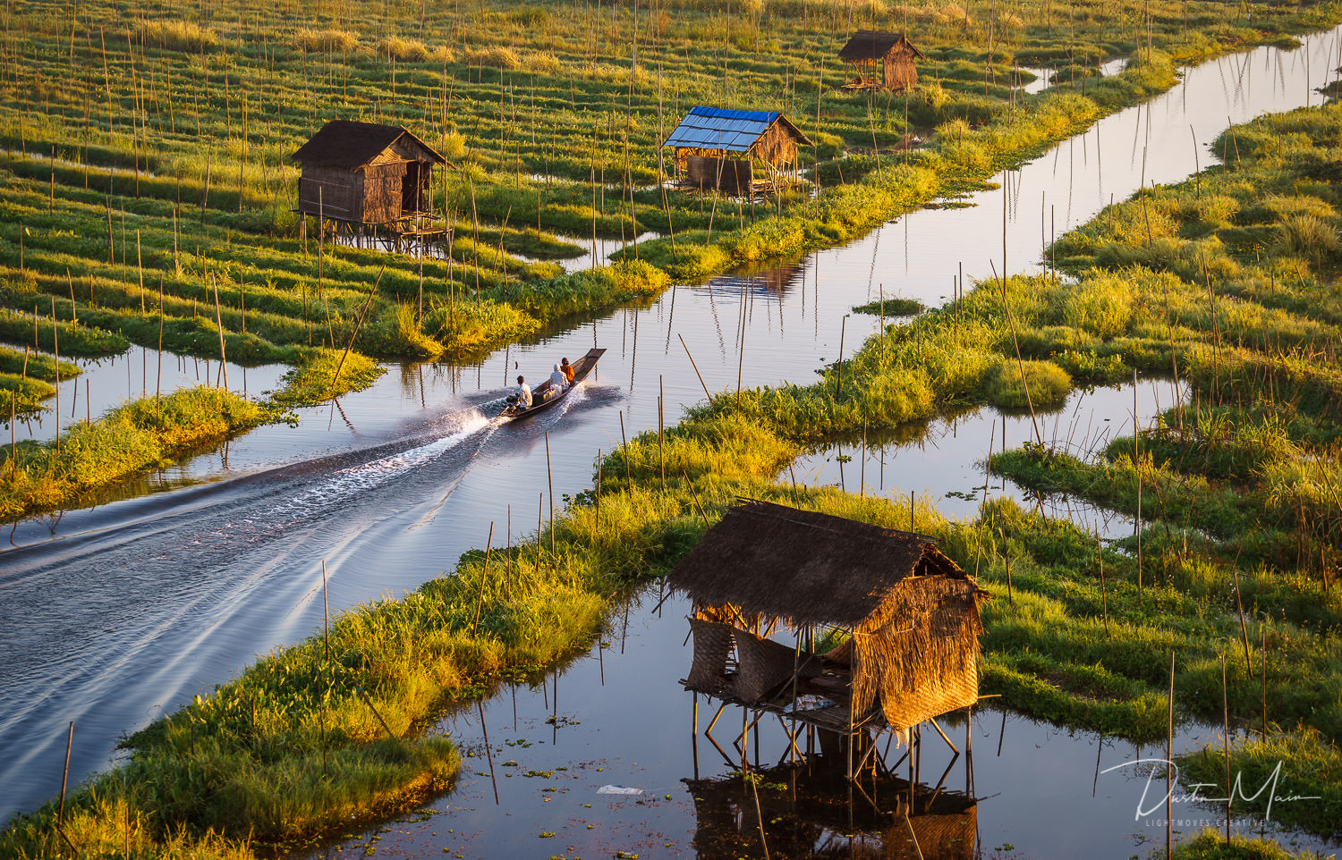 A boat heads from the village and past the floating gardens to the lake. The buildings you see here are rest houses for the farmers during the heat of the day.  © Dustin Main 2017
