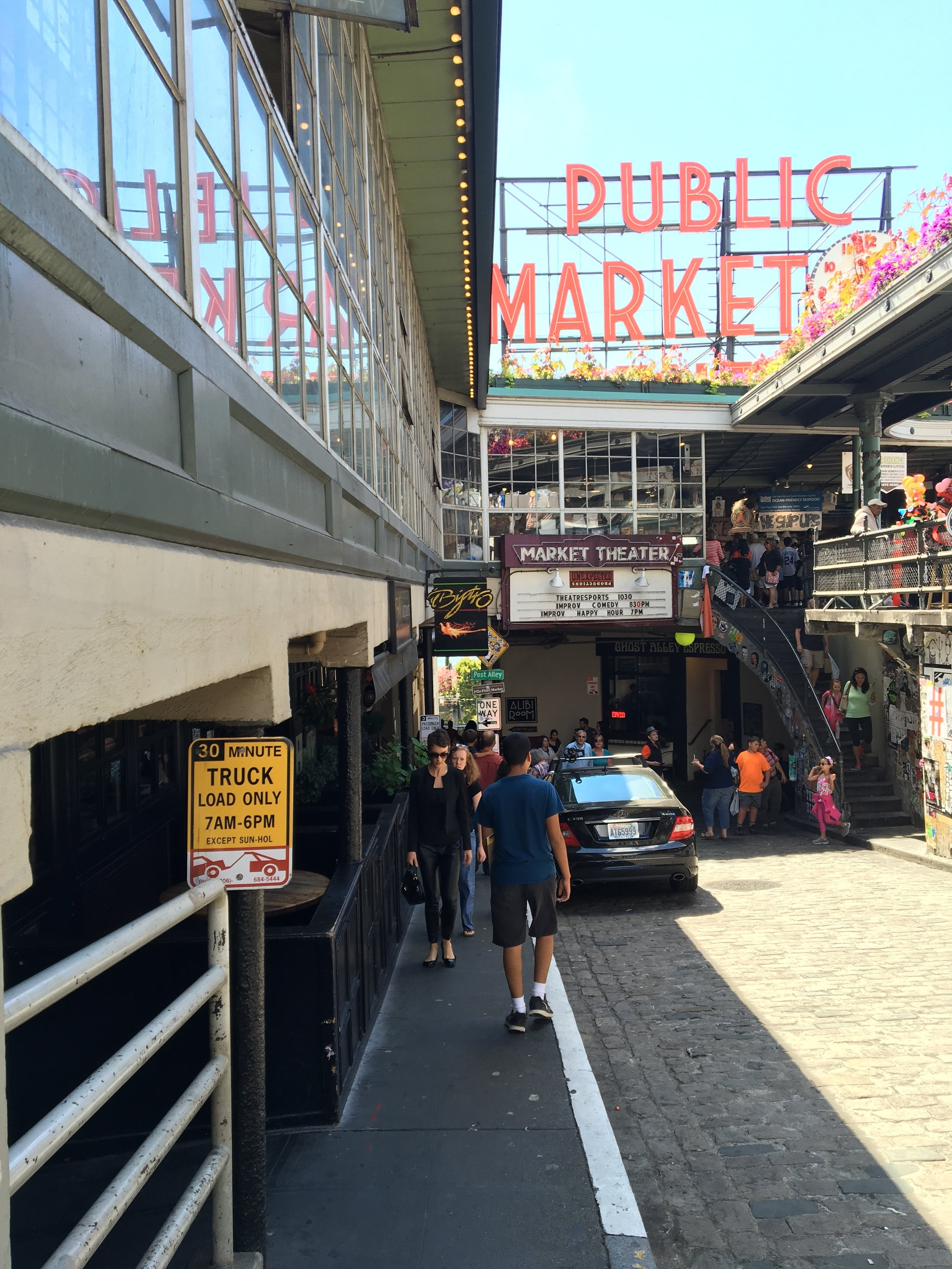 The Gum Wall is immediately to the left of the Market Theater sign.