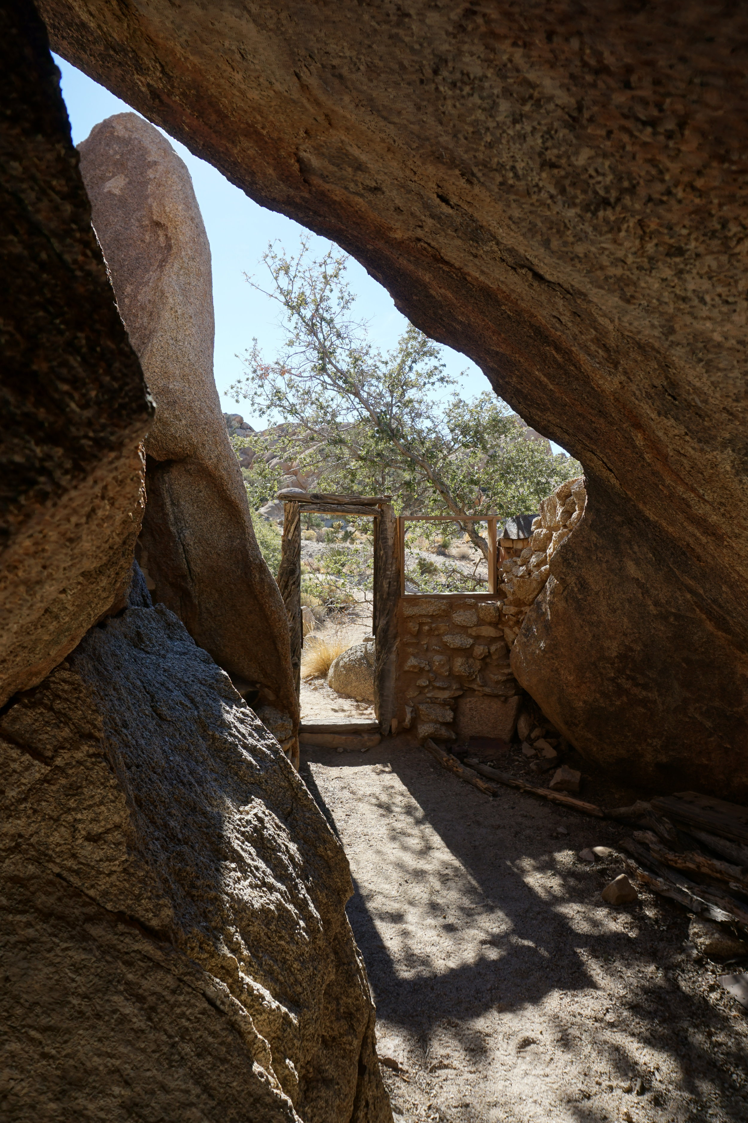 The door to the Eagle Cliff cabin is secreted between a tree and some rocks.