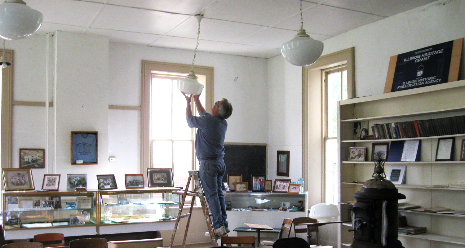 Jim Woolsey, Board member, installing new light globes as many were missing.  These were later replaced with globes found to be more similar to the original globes.